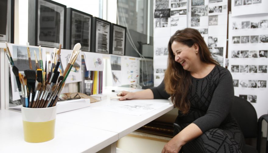 Voluspa Jarpa ríe sobre su mesa de trabajo, junto a unos pinceles y rodeada de sus obre